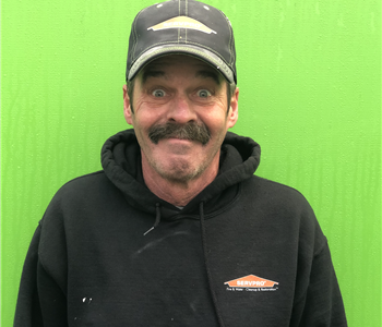 Man in SERVPRO hat mustache and beard wearing a Sweatshirt with bright green background