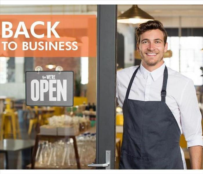 A man with an apron at the door of a restaurant