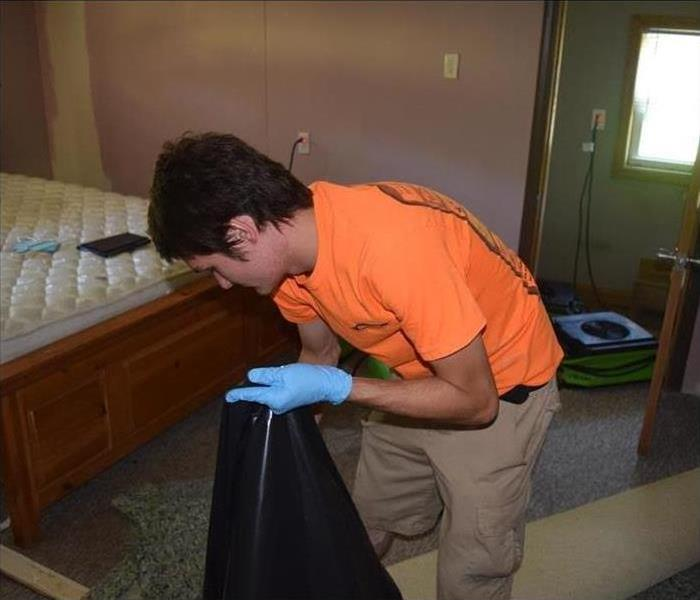 Technician with a trash bag removing unsalvageable items in a home
