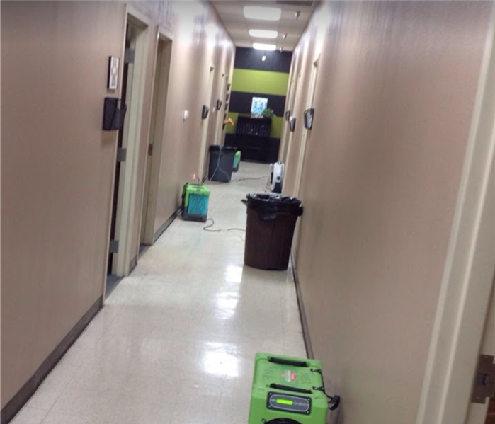 Hallway of a commercial building with air movers placed on the hallway